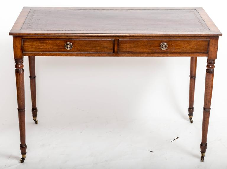 Two-drawer mahogany writing table with two drawers with brass pulls, turned legs with original brass casters and antique wine-colored leather insert. Measures: 42