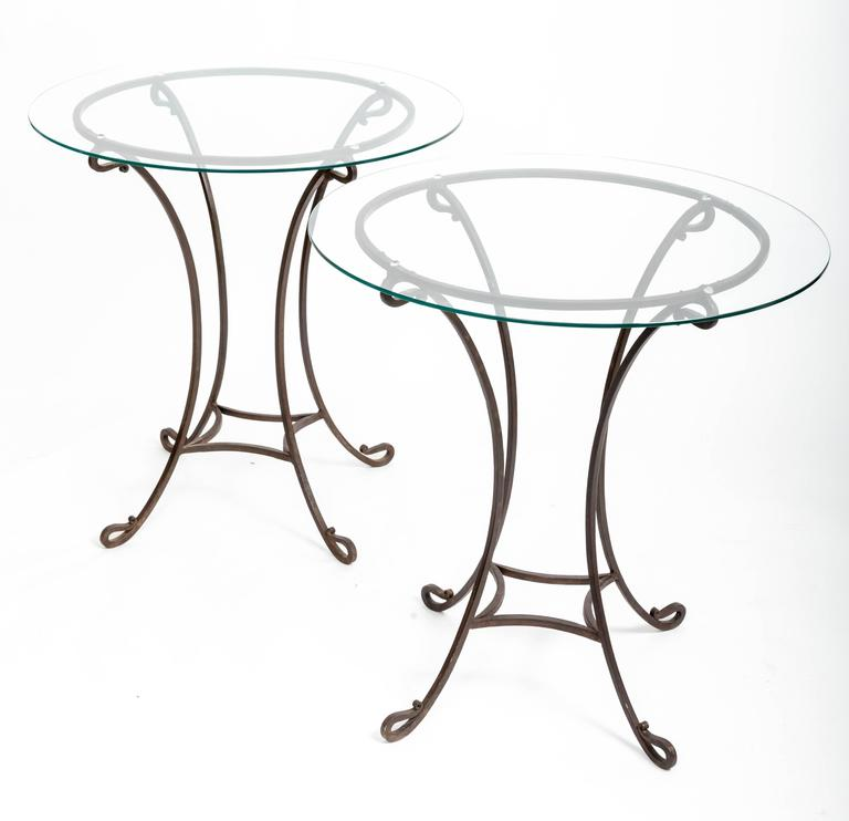 Pair of hand forged iron bases with scrolled feet and glass tops. Great as bedside tables. Can easily support two larger glass tops if desired. Measure: 30-32