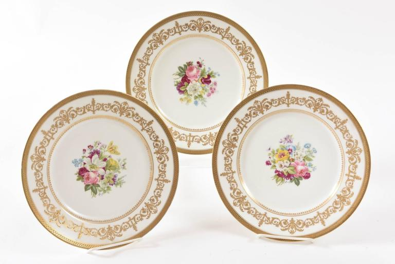 A beautiful hand-painted and artist signed set of plates by Charles Ahrenfeldt, Limoges and signed by Mireille. Each plate has a different selection of hand-painted flowers in the center and an elaborately decorated gilt collar finished with an acid