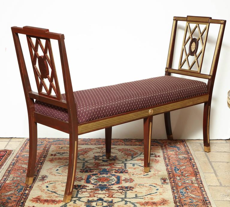 A rare pair of Russian mahogany neoclassic upholstered window benches with brass trim and molding.