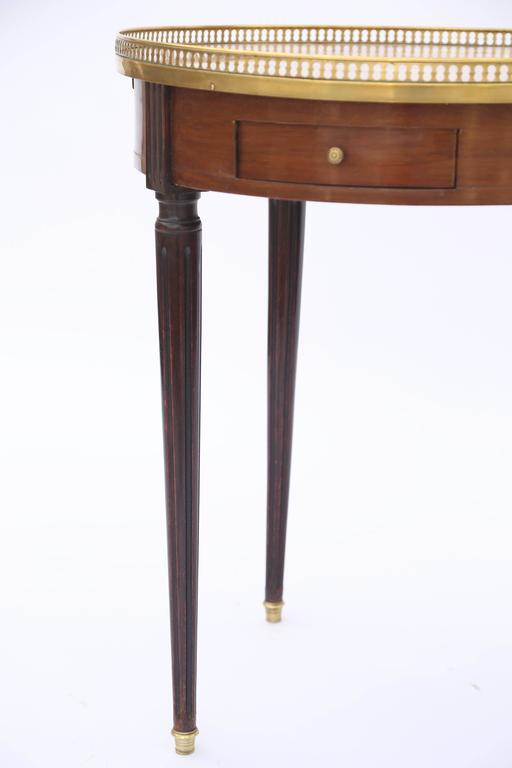 Bouillotte occasional table, having a round top of Breche D'alepmarble, surrounded by a pierced gallery of brass, on mahogany table base, with double frieze drawers, and leather-clad slides, raised on round, tapering, fluted legs, ending in brass