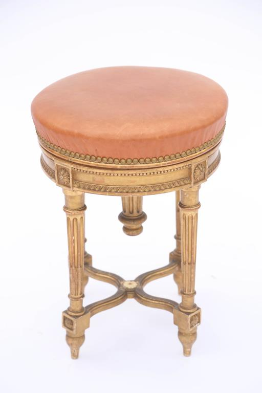Adjustable height piano stool, in the Louis XVI style, of carved giltwood, its rotating round seat upholstered in leather with nailheads, on fielded apron carved with cockbeading and gadrooning, raised on four round, tapering, fluted legs, joined by