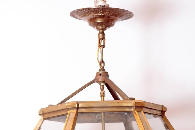 A pair of large Louis XIV style three-light gilded bronze hexagonal lanterns similar in form to those found at Versailles, together with gilt bronze ceiling canopies.  Lantern height 41 inches x 25 inches wide (with canopy 49 inches).