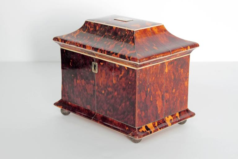 19th century English tortoise shell tea caddy with roof-form lid and bun feet. The fitted interior with two unlined compartments for tea, each lid is tortoise with bone pulls. Interior base and lid are both lined with bone. The lid with green velvet