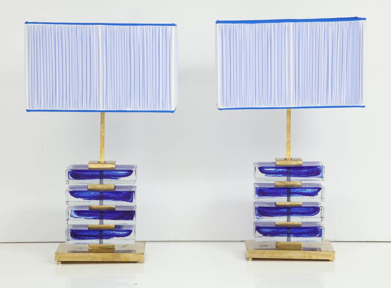 Pair of Italian solid blue and clear Murano glass block lamps with solid brass base and frame. New custom-made lampshades of blue Italian sheer silk. The lampshades were handmade in Florence, Italy. These lamps are truly a work of art! Wired for