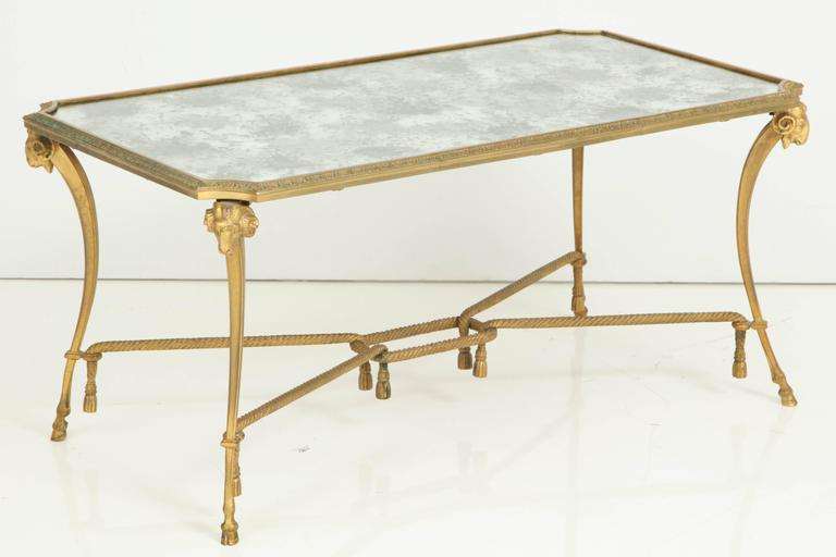Empire style 1940s Baguès gilt bronze coffee table having distressed mirrored top, hoofed feet, scrolled supports with ram's head caps and tassel accents all joined by an h-stretcher.