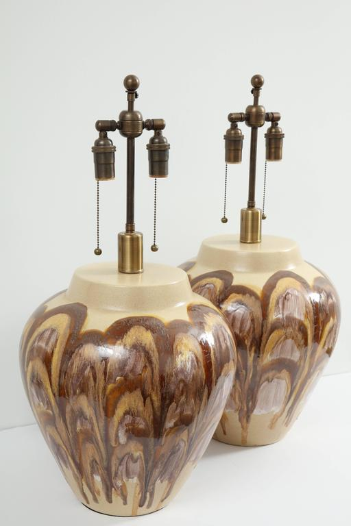 Large pair of 1960s ceramic lamps.  The large lamp bodies have a wonderful earth tone glaze which resembles oyster shells. The lamps have been newly rewired for the US with bronze finished double clusters. The ceramic portion of the lamp stands at