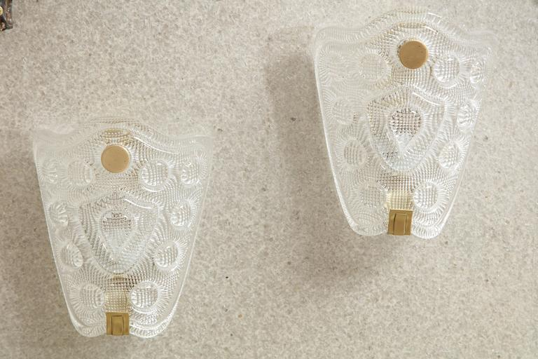 Pair of Scandinavian Modern stylized shield crystal sconces with a raised pattern. Crystal sits in a brushed brass frame with round finial detail. Rewired for use in the USA.