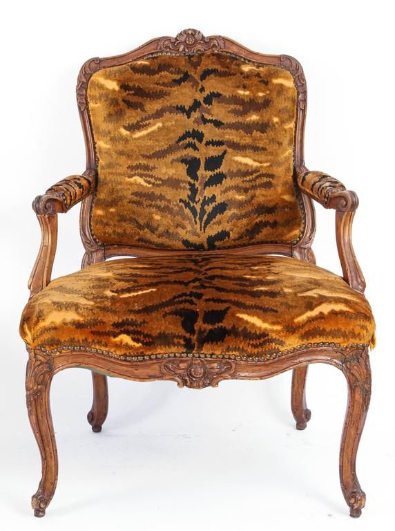 Similar Pair of 18th century French Regence carved walnut armchairs with silk velvet leopard print upholstery and nailhead detail. Each chair is slightly different in size.