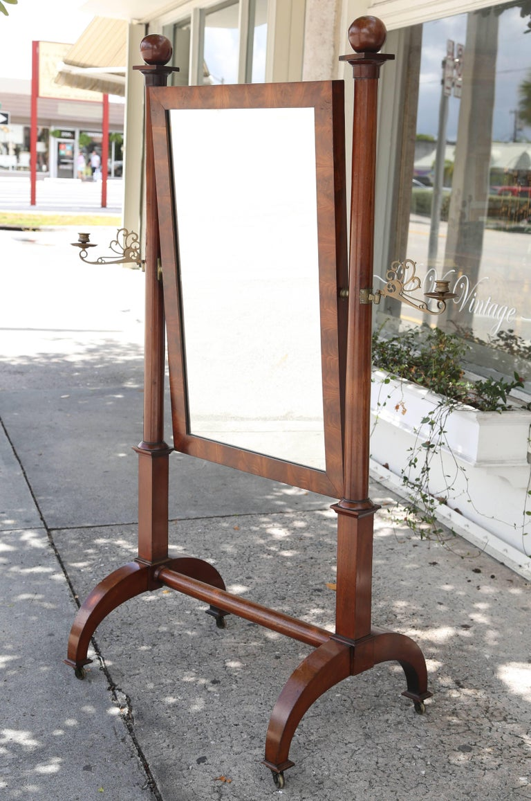 This is a superb quality cheval mirror with globular finials and columnar supports uniting a rectangular hinged frame and fitted with candle arms on a trestle base, raised on casters.