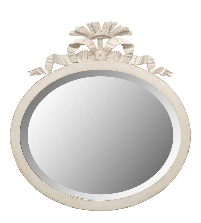 Antique Swedish Gustavian Style oval mirror painted in distressed Swedish White finish, a lovely carved bow and crown of feathers highlight the top. The mirror old with age marks, has a beveled border.  Mid-19th century, 1850-1860    Measures: H