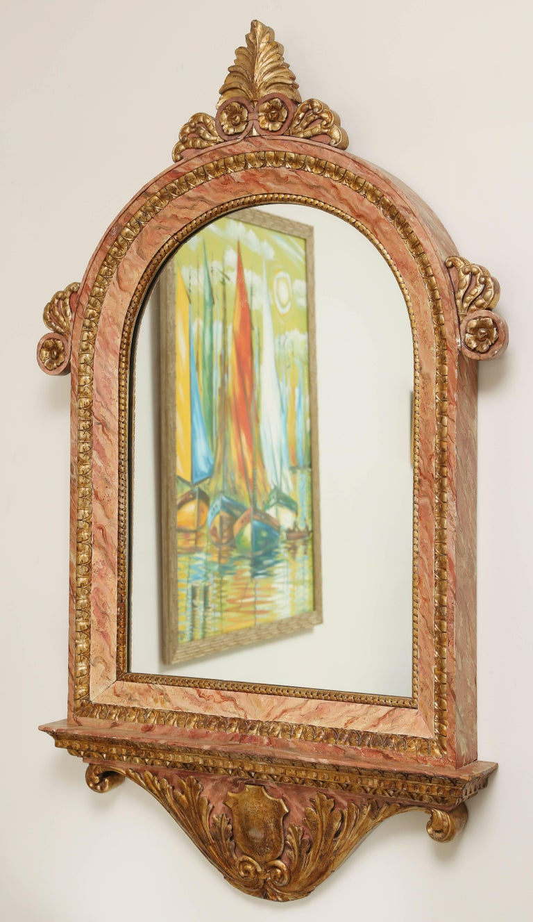 Striking late 19th century Italian carved and gilded wood mirror accented with faux marble painted finish.