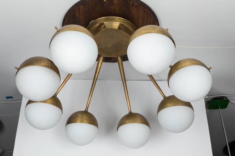 Large 1960s Italian eight-arm brass and glass chandelier Attributed to Stilnovo. Executed in patinated brass and thick 6 inch diameter matte opaline glass globes. A sculptural and refined design characteristic of 1950s Italian design at its highest