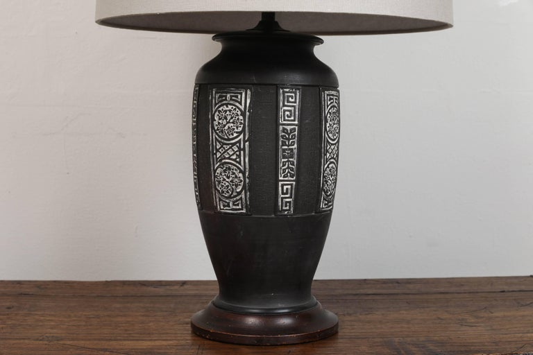 Pat McGann Gallery Vintage Chinese black ceramic. Inset designs detailed with white. Stands on a wood base. Updated hardware and twist cord wiring. Custom taupe linen shade with diffuser.