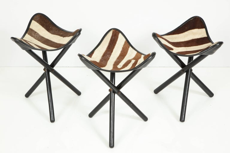 Set of three folding stools by Zimmerman of Nairobi, Kenya, circa 1950. Original leather and Zebra hide with gold stamped logo to each.