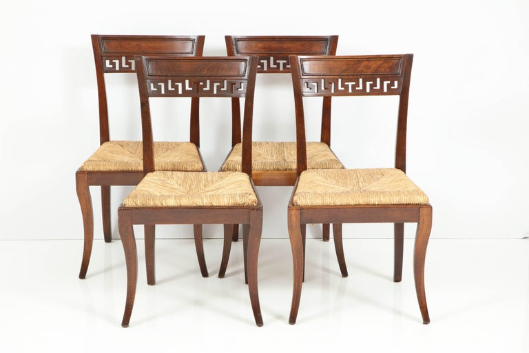 Set of four mahogany chairs with rush seats, England, circa 1900s. Measurements are: 18.75