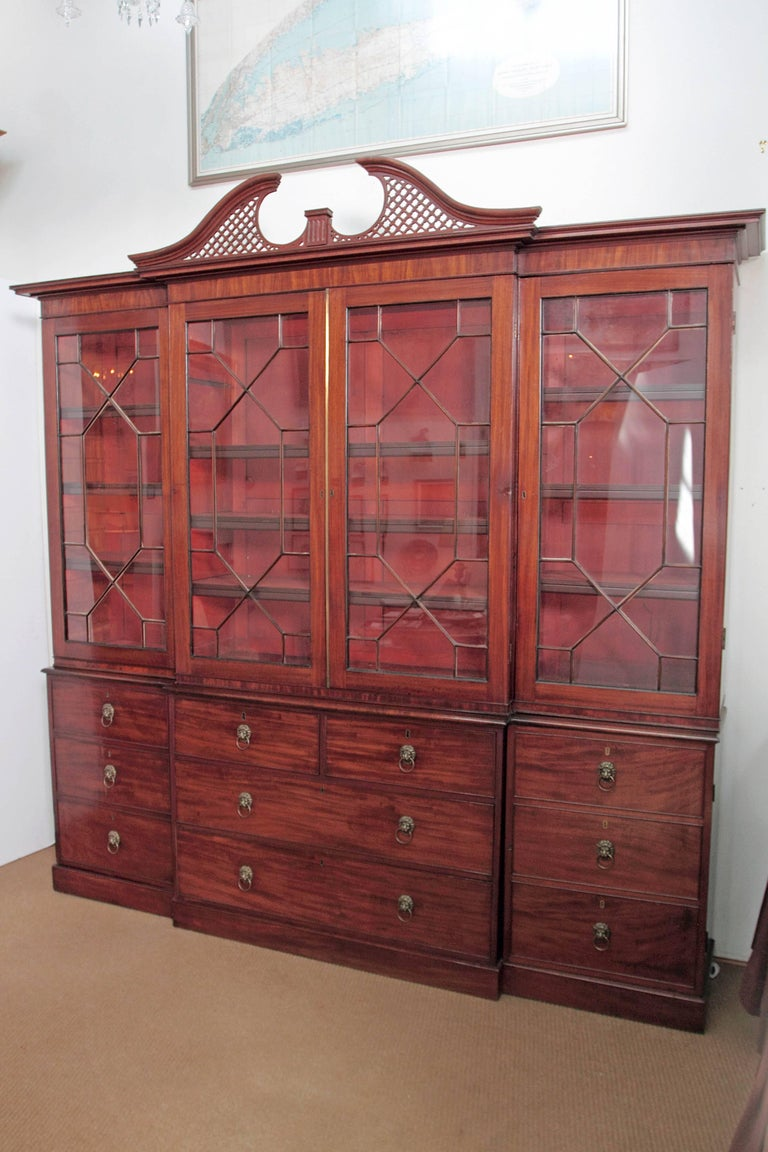 An elegant period George III mahogany breakfront bookcase / China cabinet with simple cornice and split pediment with lattice. Four (4) mullioned glass doors at the top with shelves inside. Bottom portion has two (2) small drawers above two (2)