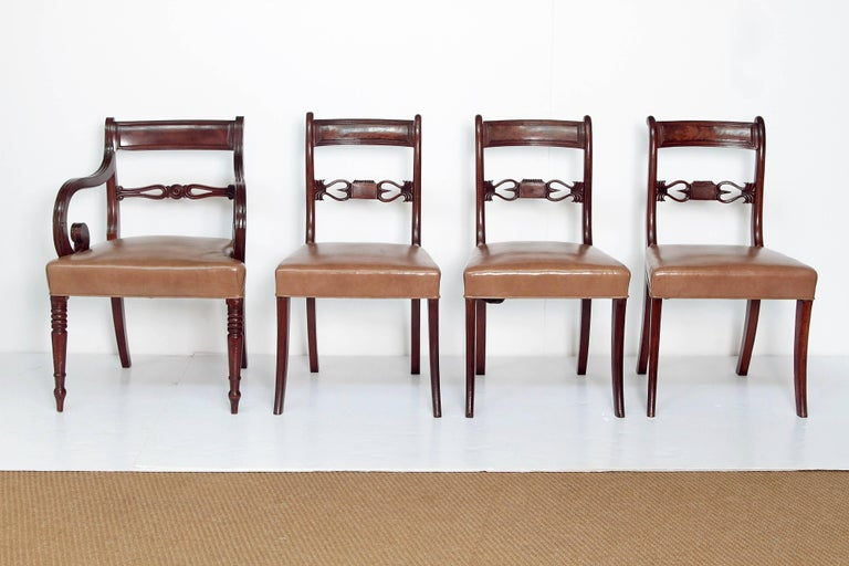 A set of eight English Regency dining chairs, six sides and two hosts. Top rails have linear rim and open carved center back support. Hosts have curled arms and turned legs. Beige leather upholstered seats.  Dimensions of Host Chairs: 32 inches
