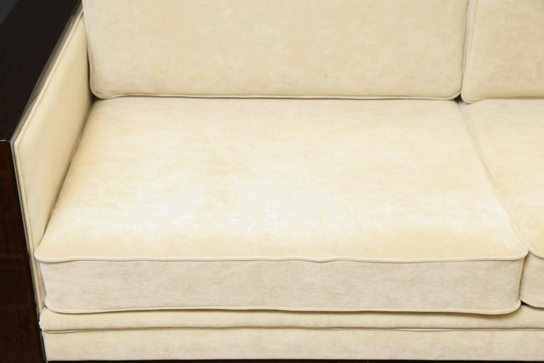 The base of the sofa is made out of Fine walnut wood. It is re-upholstered in a light yellow fabric. It has two pairs of pillows and wide wooden arm rests. The thickness of pillows provide very good back support.  Condition is excellent.