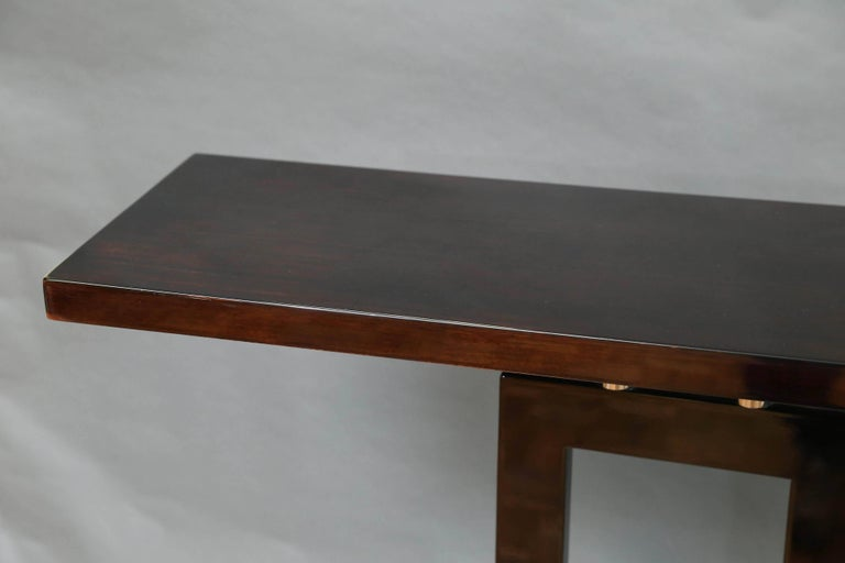 Console has a rectangular highly polished top, that presents the beauty of the wood. It has two connective hollow rectangular elements that are connecting top with a base. They are embellished with four chrome tubes on each side.  The base is the