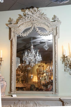 19 th century Louis XVI style gray painted mirror with torch and quiver crest