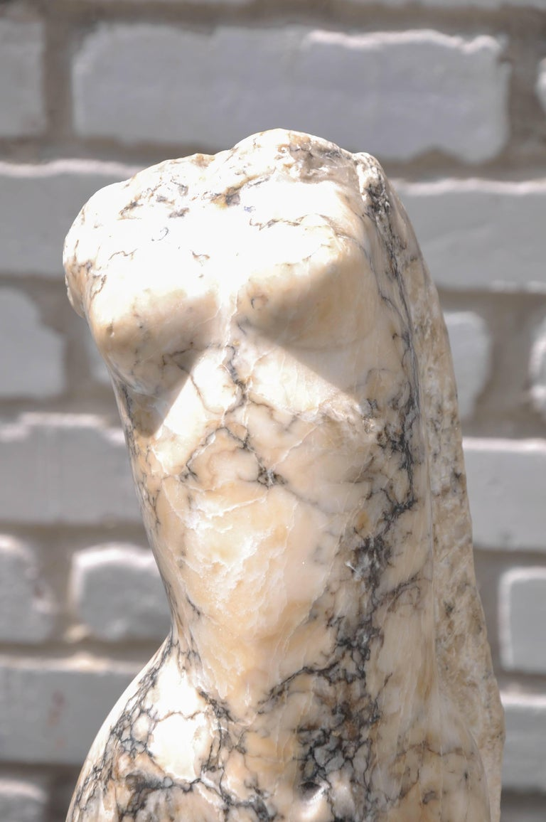 A graceful abstract headless, armless female torso Italian sculpture, hand-carved from an extraordinary cream marble with heavy gray veining, sculpted body seems to be swaying as if dancing, supported on a shapely tiered fragment black marble base