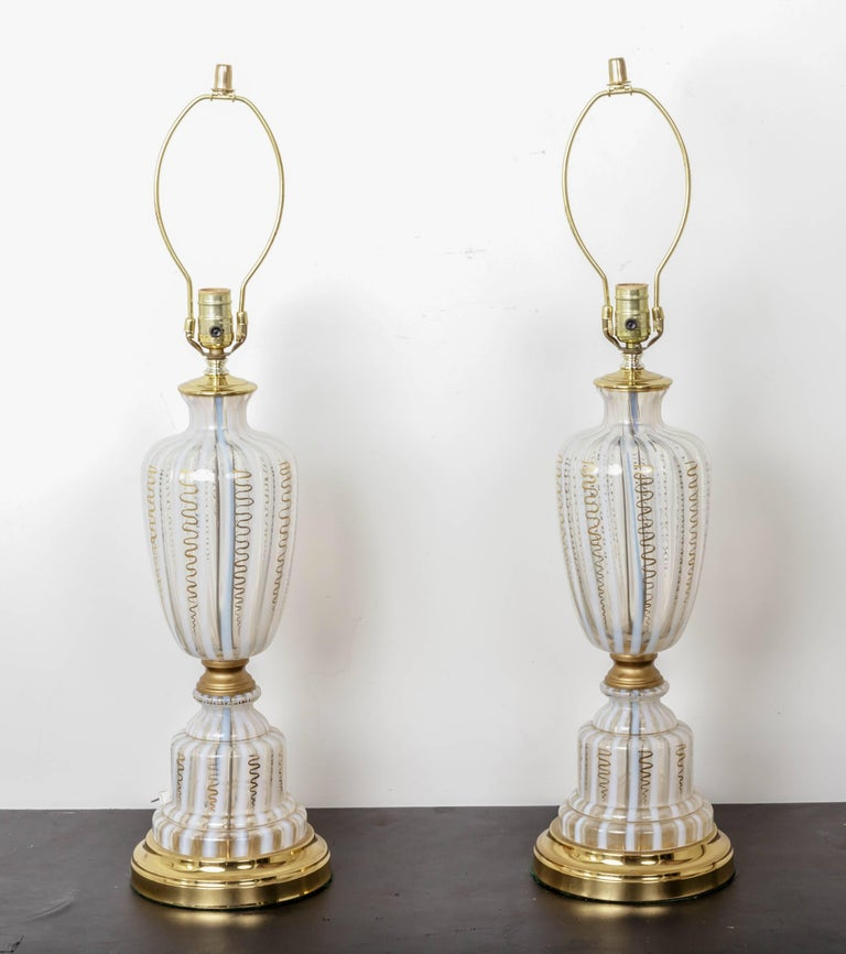 Urn shaped lamps with white stripes and gold decoration on polishes brass base.