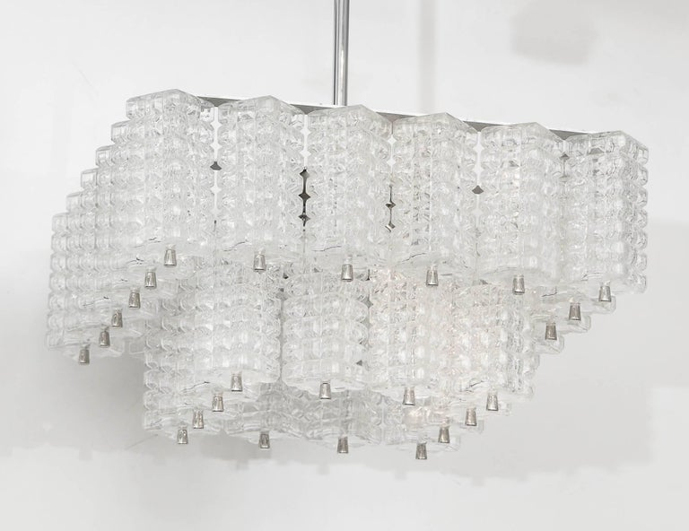 Modernist chandelier with two tiers of faceted rectangular glass elements suspended on a brushed nickel frame. Rewired for use in the USA using chandelier type bulbs.