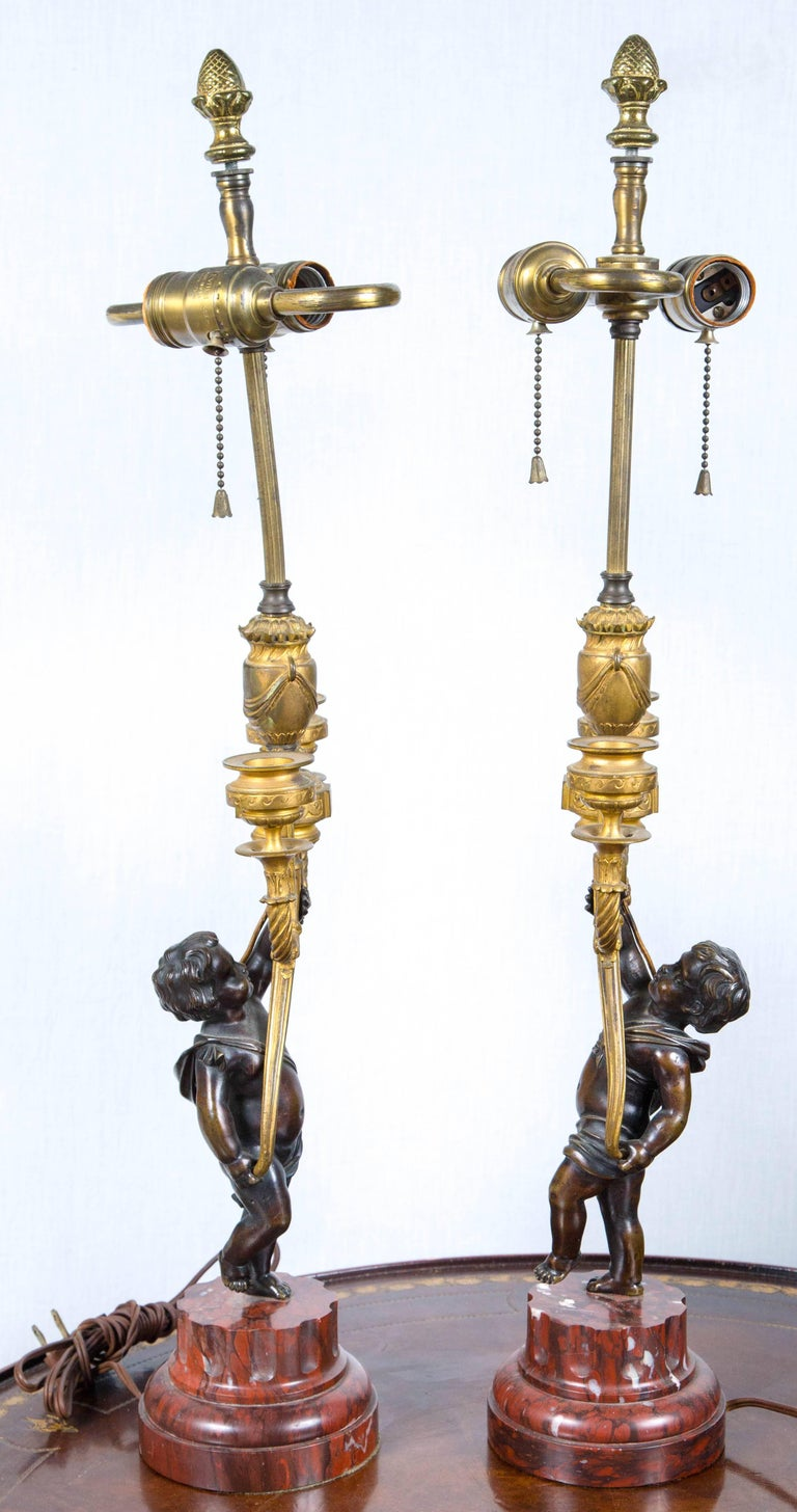 Each putto holds aloft a pair of gilt bronze candle cups. Currently wired as table lamps. They stand upon stepped and fluted rouge royal marble bases. S cluster bulb lamping. overall height 26 inches to the top of the finial 16 tall to the top