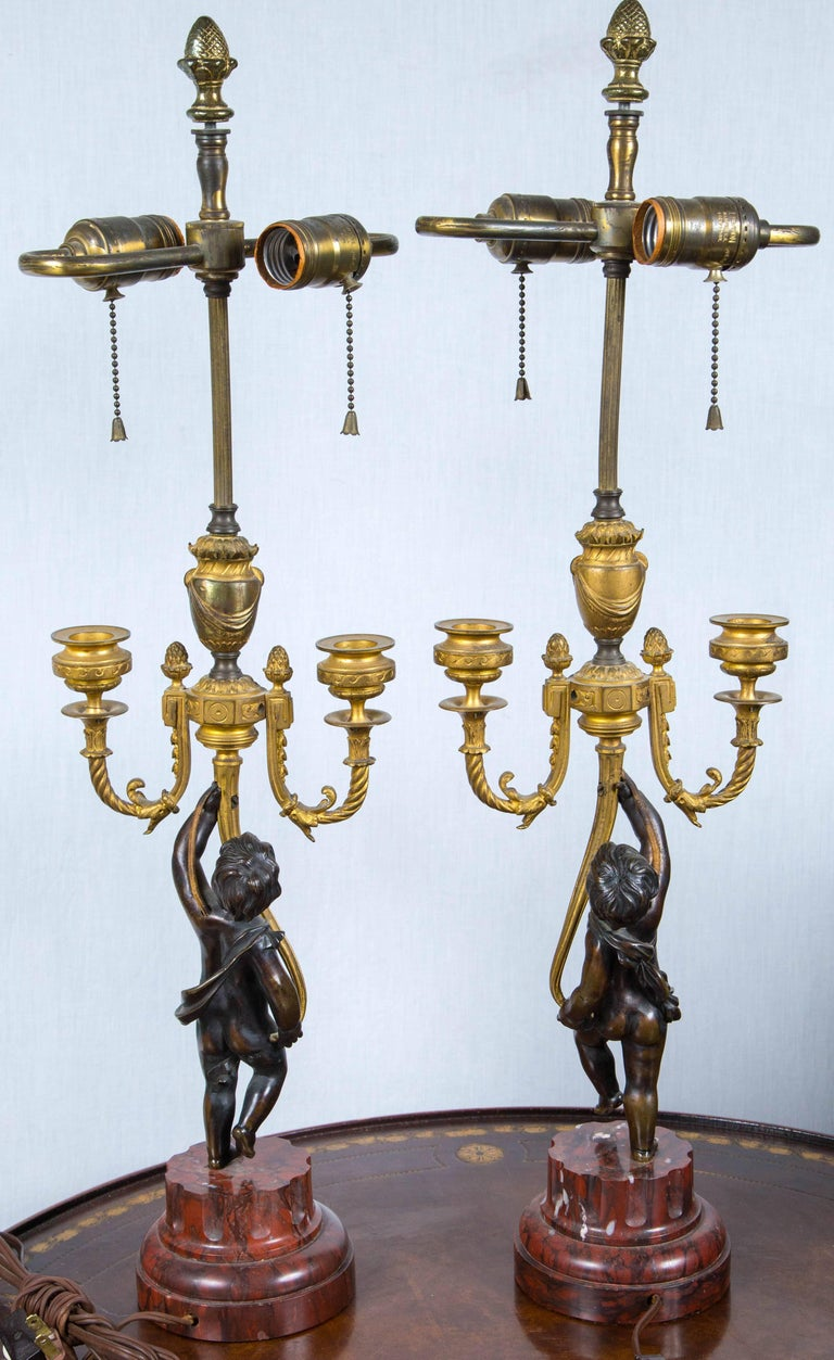 Carved Pair of Antique Gilt and Patinated Bronze Putti Candelabra For Sale