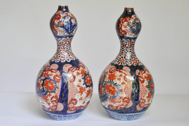 An extraordinary very rare pair of Arita porcelain double gourd garnitures. Using the original Gosai pattern, each vase is a mirror image of the other both sides of the lower bulge are detailed with Arita-red glazed chrysanthemums and peonies all