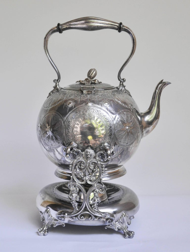 Charming English Regency style tilting tea kettle on a lamp stand. The kettle is delicately chased with a swag-like design, lovely repoussé work decorates the center of the barrel in the form of sunbursts and crests. The hinged lid has a finial