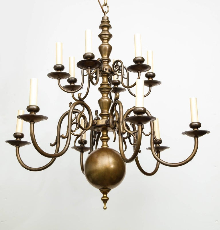 Fine turn of the century brass chandelier having two tiers of lights, both having six scrolled arms, the center shaft with balustrade turnings and ball finial, the whole with good bronze like surface and recently re-electrified.