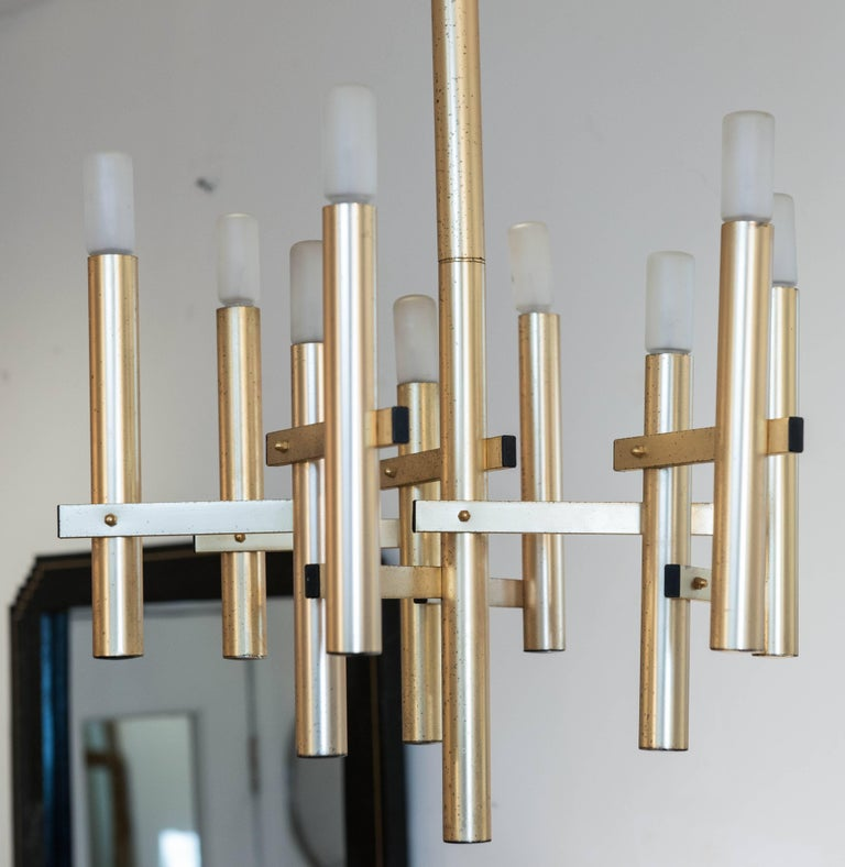 "This appealing and simple Sciolari style nine light pendant is finished in ""gold"" plate and shows wear and some spots to the finish. Original North American wiring. Matching sconces available."