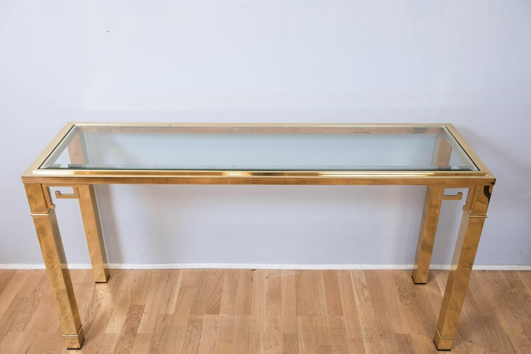 "This Classic brass console by Mastercraft with Asian inspired Greek key motif has its original 1"" beveled glass top and lacquered finish."