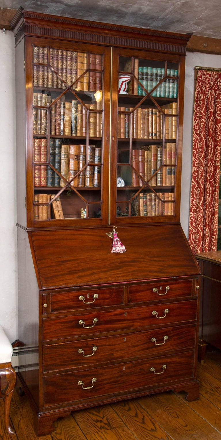 Georgian mahogany slant front glazed bookcase or secretary. The detachable broken pediment carved with dentil cornice is centered by a small platform. The upper section features two, thirteen pane, glazed doors with three original adjustable shelves