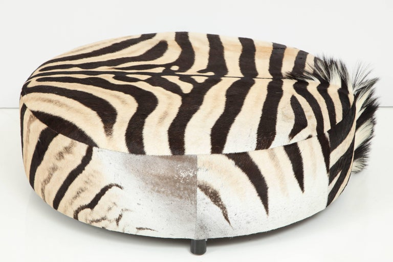 Decorative round zebra hide ottoman. Beautifully showing of the man on one side. Dark chocolate colored round wood legs.