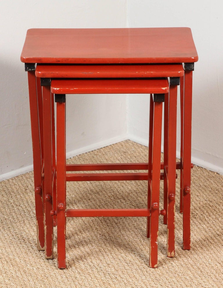 Pat McGann Gallery   Set of three slightly distressed red and black lacquer nesting tables.