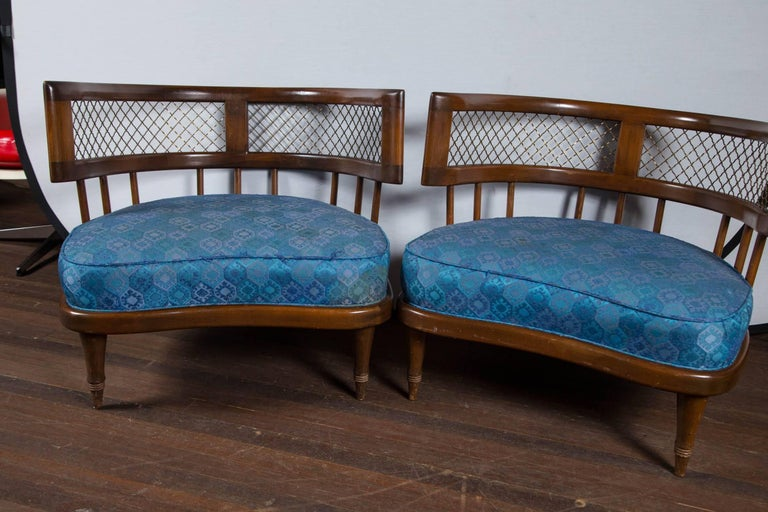 Low stylish lounge chairs in the style of Billy Haines. Mid-Century Modern curved back wood chairs. Bronze metal lattice detail below curved crest rail.