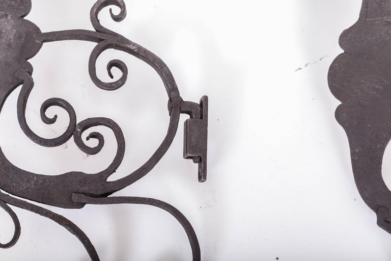A magnificent pair of 17th century European iron wall candle holders. The custom iron wall mounts are contemporary.