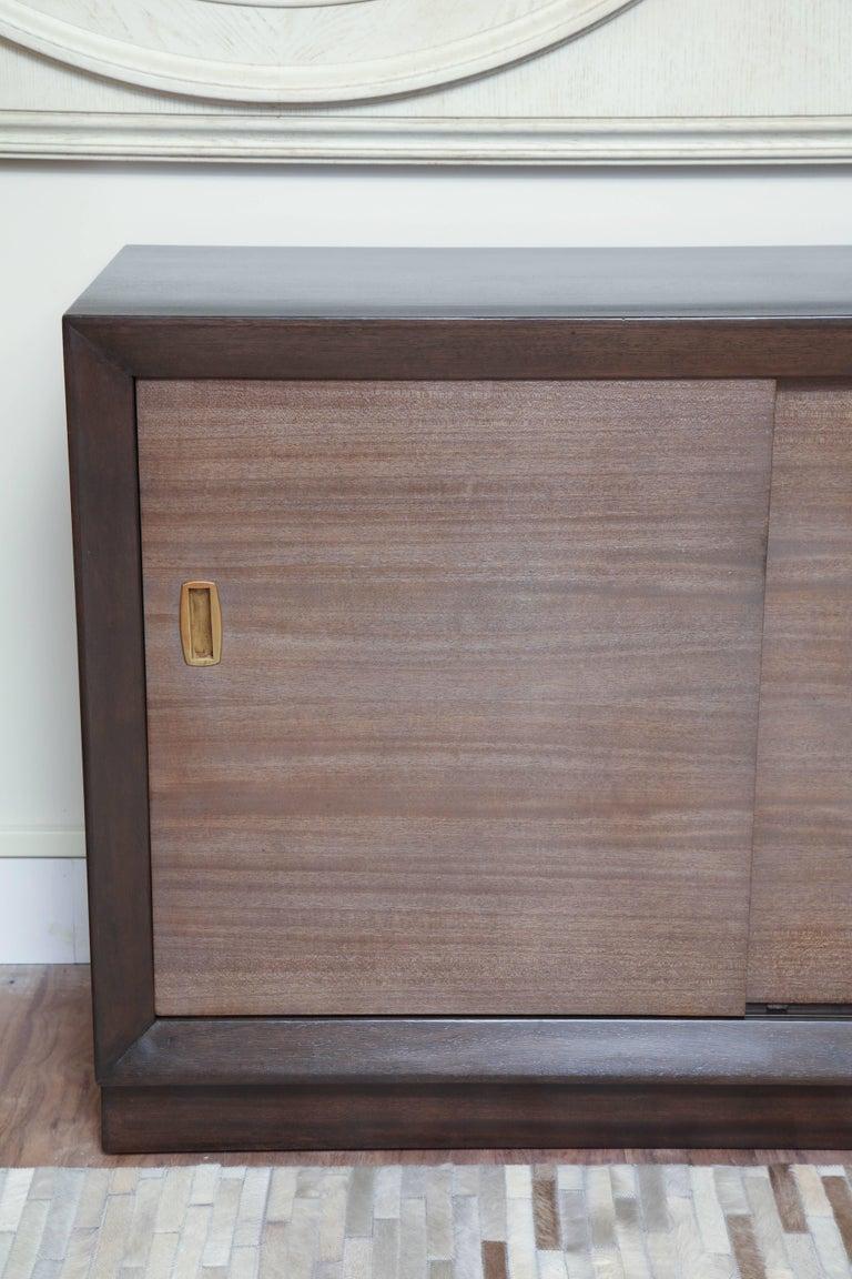 Dark walnut finished long dresser with sliding doors in the manner ofRobsjohn-Gibbings, circa 1950.