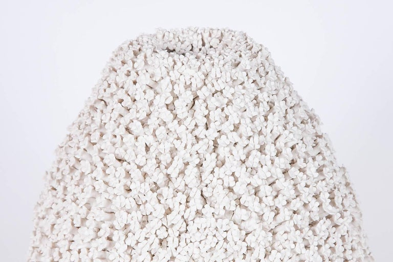 The Daphne vase is a unique hand-sculpted porcelain vessel completely covered in hundreds of individually made porcelain flowers made by the British artist Vanessa Hogge.  Vanessa Hogge breathes life into her clay in the form of dahlias,