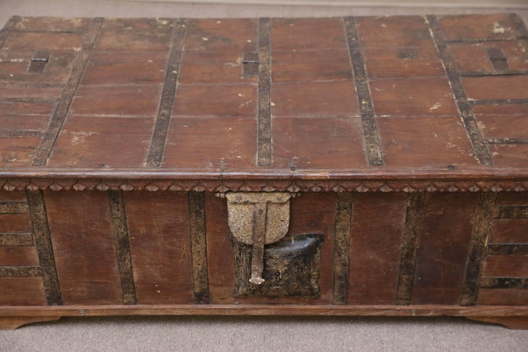 A somewhat modified teak wood dowry chest from a wealthy landlord's home in central India. The chest is reinforced with iron bars. It retains the original mechanical (not working) lock and the lifting handles. All metal works are hand-forged. The