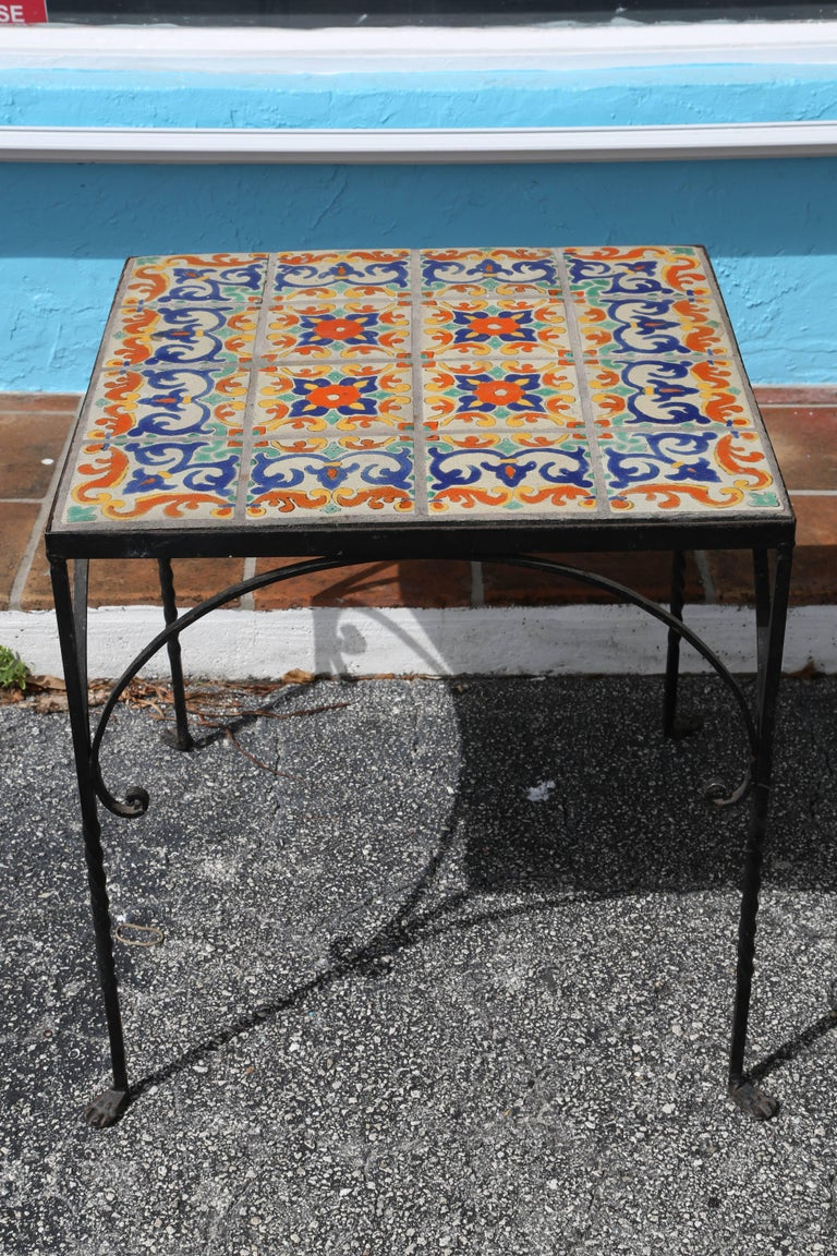 """Generously scaled with hand-wrought iron details including paw-like feet. The """"old world"""" tiles are richly colored with shades of yellow, green, orange, and blue (tile top is 25 in. square)."""