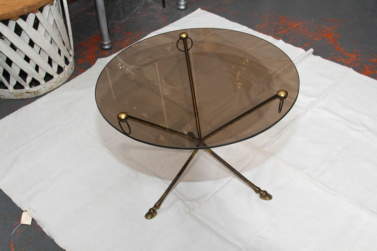 Diminutive  French smoke-glass and patinated brass side table / smoking table with a tripod base, decorative brass ring accents and exquisite deer hoof feet.