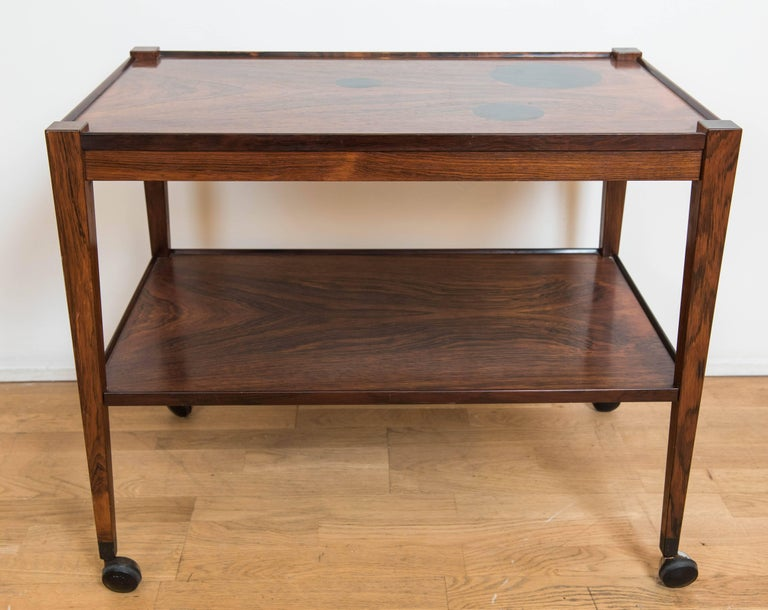 A charming and boisterous serving cart in rosewood veneer over hardwood with ebony circular decorations on the top surface as well as on the four legs. This clean and highly decorative bar cart adds distinction to many contemporary spaces. The