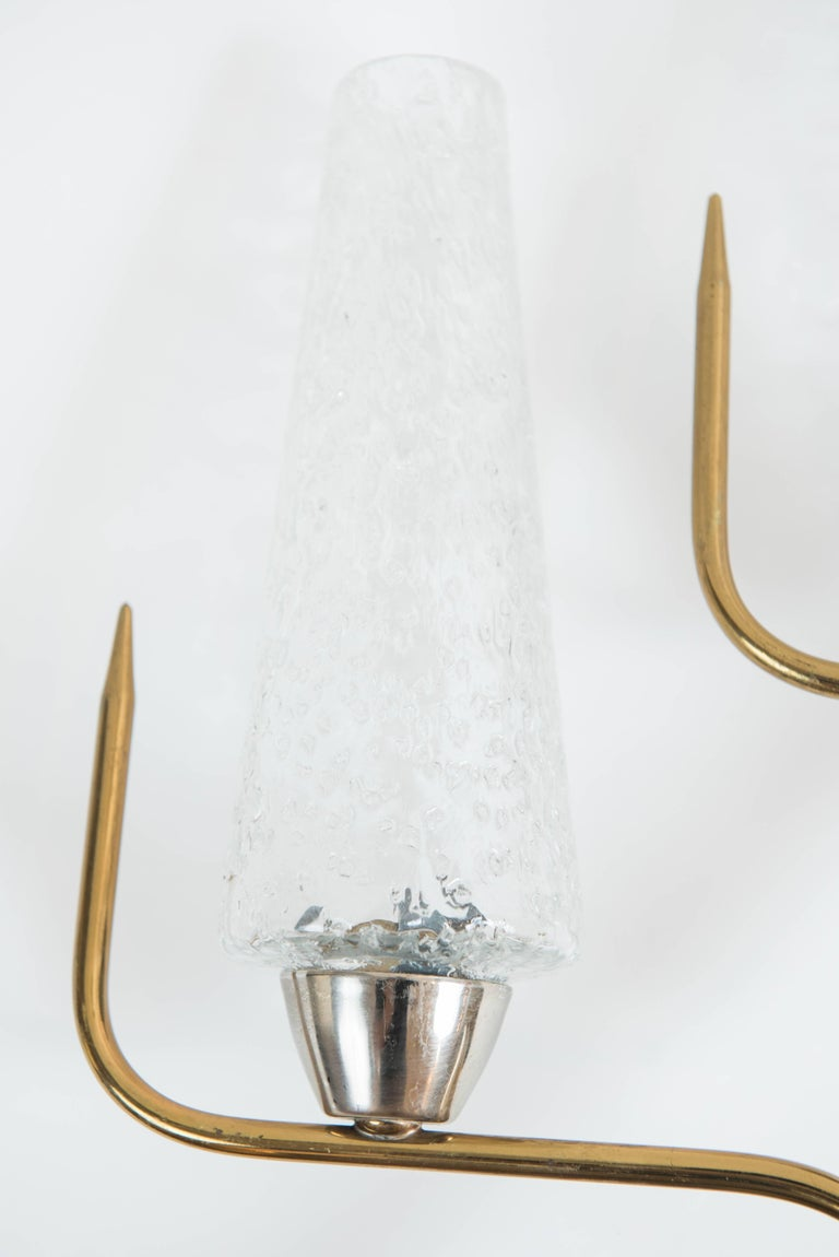 These unique and sculptural 2 light sconces are brass plated and have textured glass shades.