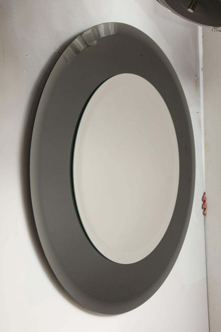 Grey glass round mirror in the style of Karl Springer.