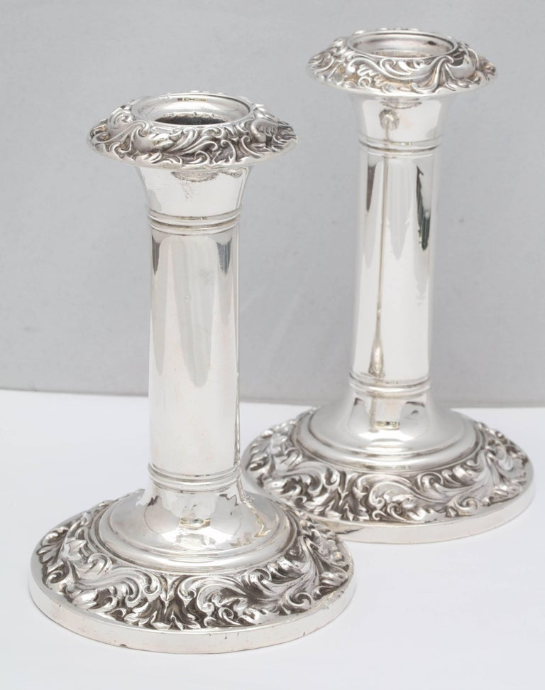 Pair of Edwardian, sterling silver candlesticks, Birmingham, England, 1906, E.L.G. - maker. Measures: 6 1/2 inches high x a little over 4 inches in diameter across the base of each. Underside of base is wood. Pretty swirled design around edge of
