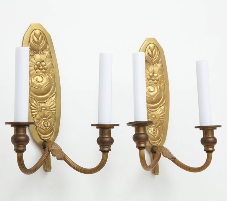 Pair of very fine bronze wall mount candle sconces or candleholders, each with two arms, and featuring a richly embossed backplate having a floral design. France, circa 1930-1940, possibly older.